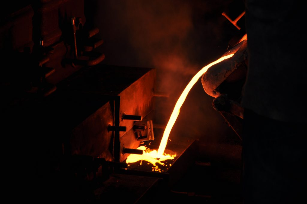 Cast iron foundry - pouring molten metal into mold
