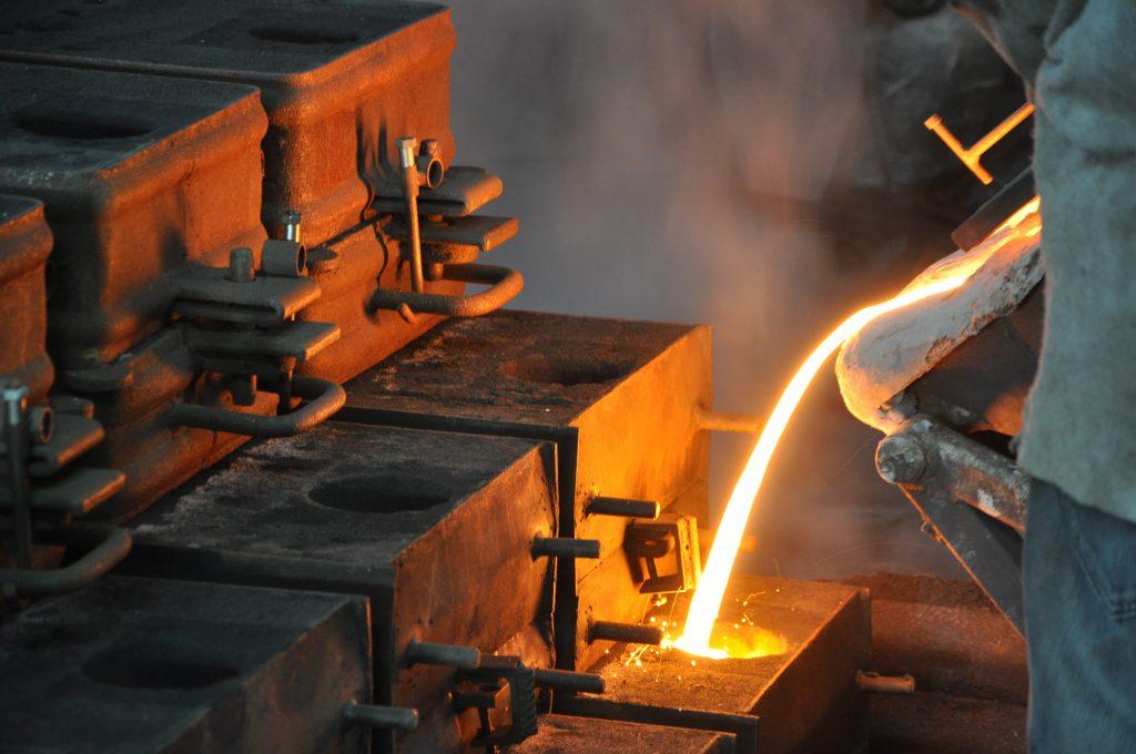 Pouring molten grey iron into sand mold